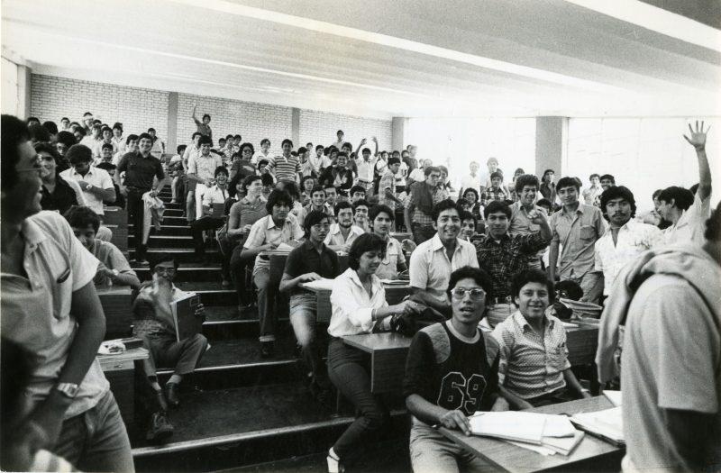 Alumnos de Estudios Generales Ciencias posan para un retrato grupal en una de las clásicas aulas escalonadas, al final de su clase. Comienzos de los años ochenta. El ambiente es casi totalmente masculino.